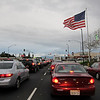 Mar 22: Sitting in traffic, waiting for the light to change, and this gigantic American flag caught my eye. It is huge--if it were lying on the ground, I think you could park four cars on it. Somehow the idea of all these billions of cars burning gasoline under the American flag on a stormy day,all the red and white lines of cars and red lines of lights and white lines on the road and the red & white stripes in the flag above, appealed to me. Opened the car window, leaned out, took a few shots trying to get the best display of the flag in the wind, and here it is.