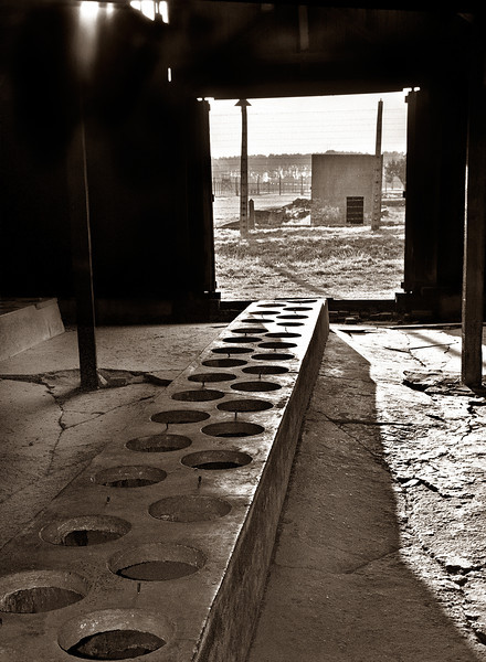 Birkenau--Row of toilets in the camp latrine.  Sanitary conditions were so horrible that Nazis were afraid to enter, so the latrine served as the heart of the black market and inmates' resistance movement.