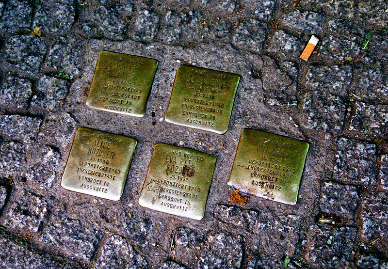 "Berlin--Examples of small brass memorials set in streets around the city.  These people were all from the same family.  Plaque on lower left says: ""Here lived Alice Kozower, born 1934, deported 1943 to Theresienstadt, murdered in Auschwitz."""