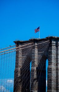 Brooklyn Bridge Tower with US Flag Blowing in the Summer Wind on a Clear Day