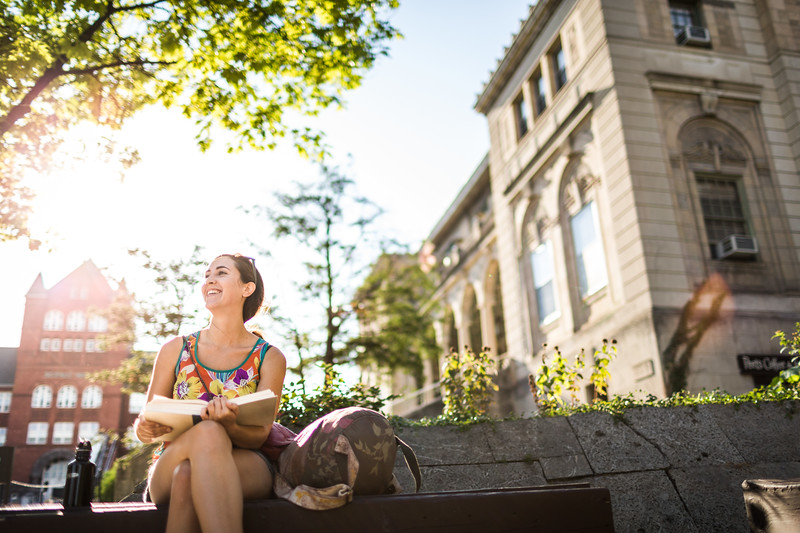 A woman sitting outside holding a book.