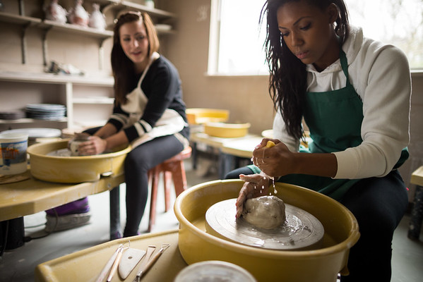 Two woman performing ceramic pottery making.