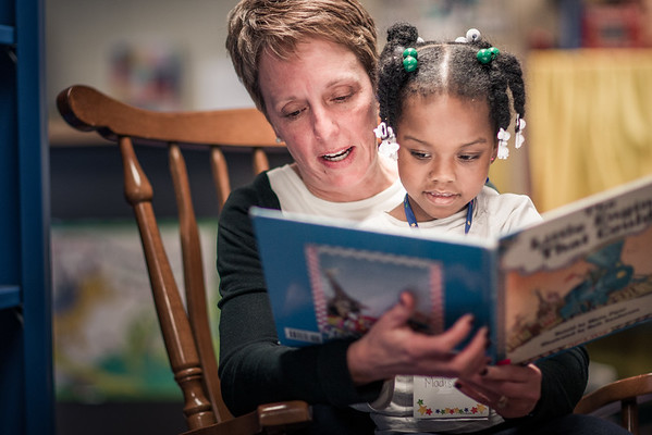 Teacher reading to student in school library.