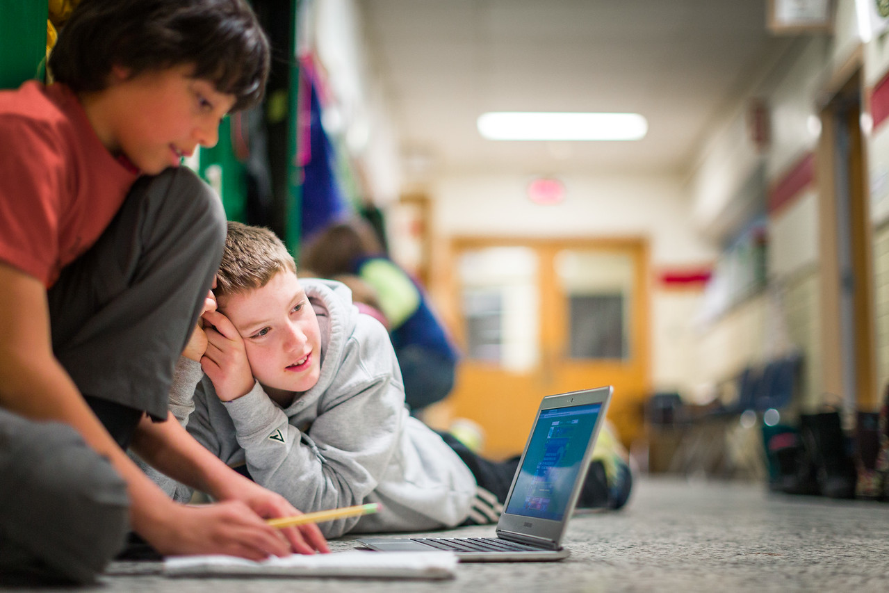 Two young boys working on a group assignment together.
