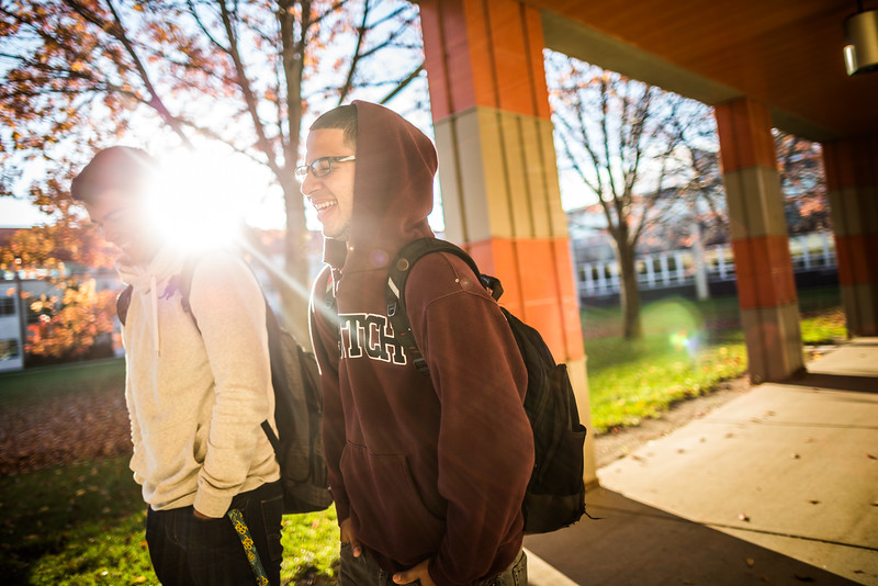 Two students walking outside of school laughing.