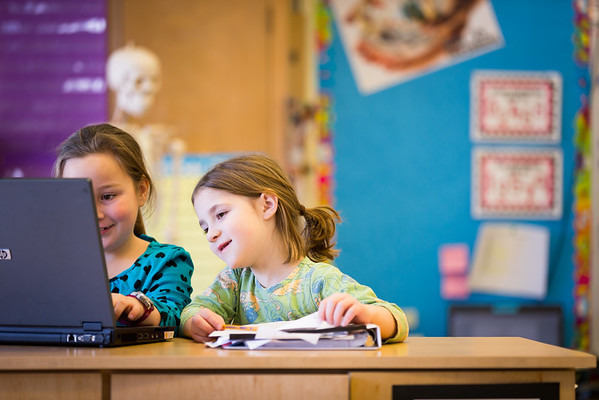 Two young girls in elementary school working together.