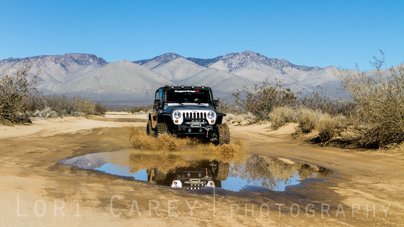 Jeep reflected in puddle, El Paso Mountains in the Mojave desert, California