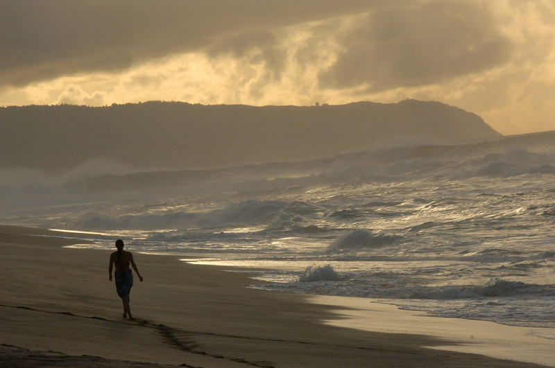 A women walks along the surf  at dusk with 6 to 10 foot waves breaking in the distance at Sunset Beach Hawaii, Wednesday, Dec. 6, 2006. (AP Photo/Lucy Pemoni)