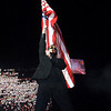 Bono, singer of band U2, enters the stage holding a flag for the opening song of his concert at Aloha Stadium in Honolulu, Hawaii, December 9, 2006. The Hawaii concert was the last show for U2's Vertigo Tour. REUTERS/Lucy Pemoni  (UNITED STATES)