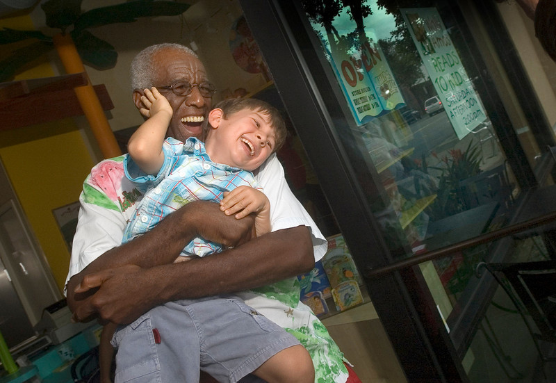Wally Amos hugs Jayson Weidmann in the doorway of his cookie store after his weekly children's book reading on Saturday, June 16, 2007 in Kailua, Hawaii. Amos, who created the famous Amos cookie empire three decades ago eventally lost ownership of the company_ as well as the rights to use<br /> the catchy name _ is now selling muffins. (AP Photo/Lucy Pemoni)