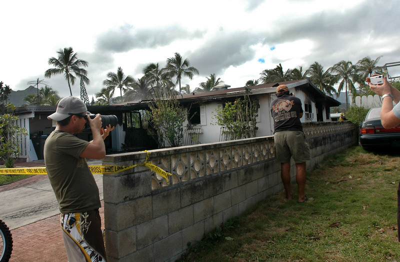 """Photographers shoot the burned out shell of the home rented by Evangeline Lilly, a leading cast member of ABC's TV series """"Lost"""" in Kailua, Hawaii, Dec. 20, 2006. The fire started about 6:30 this morning but Lilly and a housemate  had already left to film about an hour away on the North Shore. (AP Photo/Lucy Pemoni)"""