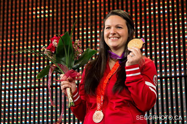 """SEGO2018-1203-015 3 December 2018  The International Olympic Committee and the Canadian Olympic Committee officially presented Christine Girard her London 2012 Olympic gold and Beijing 2008 Olympic bronze medals in weightlifting. The medal ceremony was held at the National Arts Centre in Ottawa, Ontario, Canada.   info from https://olympic.ca/press/christine-girard-awarded-london-2012-and-beijing-2008-medals/ :  """"Girard was initially awarded the bronze medal at London 2012. After the International Olympic Committee ordered retesting of more than 1500 urine samples from Beijing 2008 and London 2012, the samples from two athletes who placed ahead of her, Maiya Maneza of Kazakhstan and Svetlana Tsarukaeva of Russia, were found positive for doping. They were disqualified, losing their placings and medals. Girard was confirmed as the London 2012 Olympic champion in April 2018.  In late 2016, Girard was awarded the bronze medal from Beijing 2008 after Irina Nekrassova of Kazakhstan was stripped of her silver medal for testing positive for banned substances. Girard had initially placed fourth in the event.""""  © Serge Gouin 2018  www.segophoto.ca"""