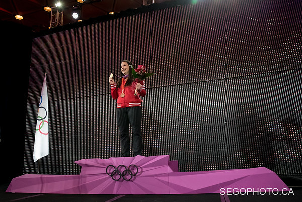 """SEGO2018-1203-011 3 December 2018  The International Olympic Committee and the Canadian Olympic Committee officially presented Christine Girard her London 2012 Olympic gold and Beijing 2008 Olympic bronze medals in weightlifting. The medal ceremony was held at the National Arts Centre in Ottawa, Ontario, Canada.   info from https://olympic.ca/press/christine-girard-awarded-london-2012-and-beijing-2008-medals/ :  """"Girard was initially awarded the bronze medal at London 2012. After the International Olympic Committee ordered retesting of more than 1500 urine samples from Beijing 2008 and London 2012, the samples from two athletes who placed ahead of her, Maiya Maneza of Kazakhstan and Svetlana Tsarukaeva of Russia, were found positive for doping. They were disqualified, losing their placings and medals. Girard was confirmed as the London 2012 Olympic champion in April 2018.  In late 2016, Girard was awarded the bronze medal from Beijing 2008 after Irina Nekrassova of Kazakhstan was stripped of her silver medal for testing positive for banned substances. Girard had initially placed fourth in the event.""""  © Serge Gouin 2018  www.segophoto.ca"""