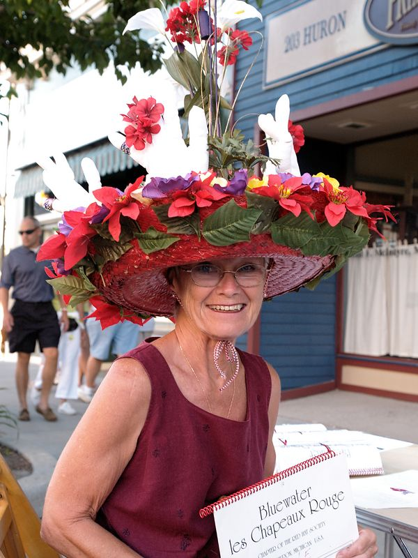 <font size=3>One of the members of the local Red Hat Society sports her chapeaux and their recent fundraiser - a calender of nudes with their membership as the models.</font>