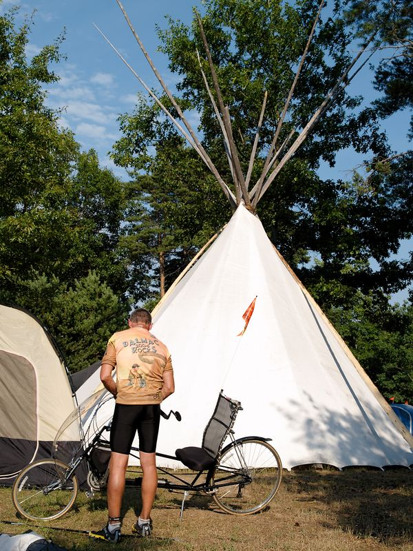 <font size=3>A rider tends to his bike in front of a teepee on the campsite.</font>