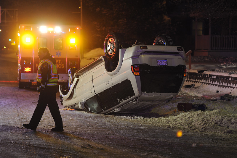 A Moline firefighter walks past an upside-down SUV on Avenue of the Cities near its intersection with 25th Street. The sole occupant of the SUV was taken to the hospital by ambulance. The SUV was westbound on Avenue of the Cities and slid off the road on a curve, breaking a fire hydrant and running into a retaining wall along the north side of the street before flipping over shortly after 7 p.m. Monday, Feb. 17, 2014.