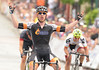 Men's Pro winner Daniel Holloway holds his arms up in victory after winning the rain-shortened Quad Cities Criterium in the Village of East Davenport on Memorial Day, Monday, May 26, 2014.