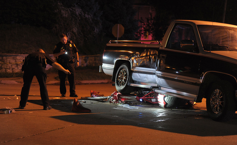 Moline police officers use flashlights to light up a crushed custom motorcycle under a Chevrolet pickup in the intersection of 15th Street and 13th Avenue on Wednesday. The motorcyclist was taken to a hospital for severe head injuries and multiple lacerations after striking the driver's side of the pickup at 8:32 p.m., according to police. Police said the motorcyclist was traveling north on 15th Street when he struck the truck heading west at the intersection of 13th Avenue. Police said they did not believe the motorcyclist was wearing a helmet. No further details were available Wednesday night; the investigation is ongoing, police said.