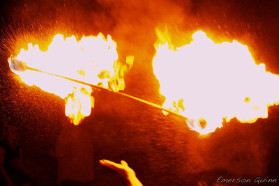 Fuel explodes from a flaming fire baton in mid-air