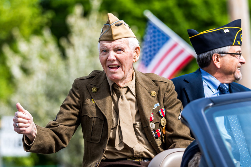 Honored: World War II veteran Frankie Flanders, wearing his original uniform, gives a thumbs up to the crowd during Norway's Memorial Day parade. Flanders, who served in the South Pacific, was the grand marshall of the parade. Riding with Flanders is keynote speaker Joel Dutton, lead administrator of the Maine Veteran's Home in South Paris.
