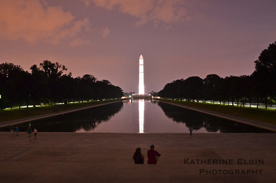 A couple watches the sunset at from the steps by the Lincoln Memorial.