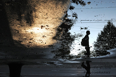 A student is reflected in a puddle at Princeton University.