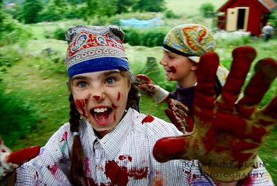 Two young Swedish girls run past the photographer after painting a barn with red 'falun' paint.