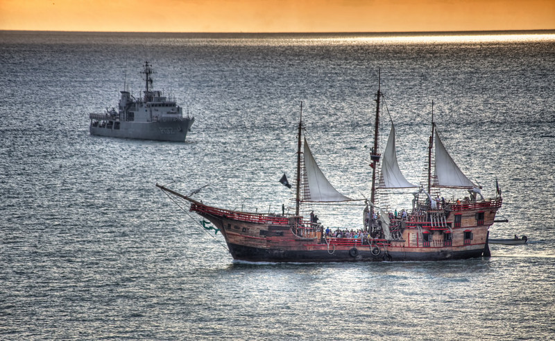 Mexico - Puerto Vallarta<br /> <br /> Pan American Games torch being transported to shore by charter vessel whilst being overseen by a decidedly different boat.  I wish I could tell you that the naval ship fired upon the charter.. it's a much better photo with that narrative...