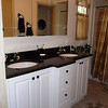 "After... New clean bright white cabinets with elegant ""bump-out"" & granite counter top with white porcelain sinks.  New tile floors and a new showerl"