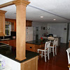 """After... redesign floor plan; remove soffit, move appliances, remake island, cherry wood floors & new all wood cabinets and granite counter tops.  Beautiful!  Also, partial removal of wall into living room, new window over sink and """"French doors"""" instead of sliders."""