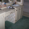 "Before... old laminate ""low"" cabinets, no shower, carpet in bathroom & laminate counters."
