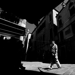 Extremes: Narrow streets and lanes, the strong Italian light at the height of summer creates extremes of light and dark. Textures and mid-tones are accentuated in between as people appear and disappear from and into the shadows.  ©Paul Campbell.