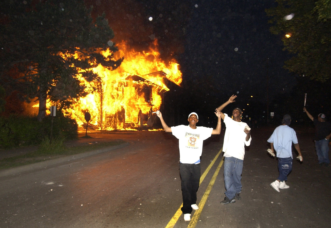 People demonstrate in front of a burning house on Empire Street shortly after dark in Benton Harbor Tuesday night on 6/18/2003.  (Photo by Mark Bialek)