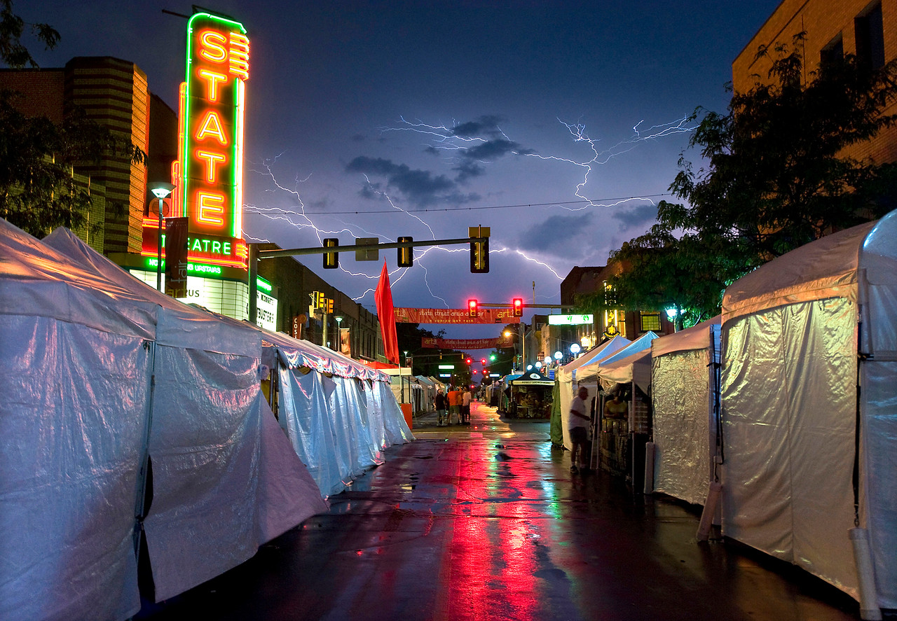 Lightning strikes over the corner of State and Liberty streets in downtown Ann Arbor, Michigan forcing artists to close up their booths early during the July 2010 Art Fair.  Ann Arbor had one of the first art fairs in the country, starting in 1960.  The 2011 Art Fair takes place from July 20-23.  (Photo by Mark Bialek)