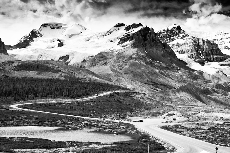 View of Saskatchewan and Athabasca Glaciers in the Columbia Icefields. The Athabasca is the most-visited glacier on the North American continent. Situated across from the Icefield Centre, its ice is in continuous motion, creeping forward at the rate of several centimeters per day. Spilling from the Columbia Icefield over three giant bedrock steps, the glacier flows down the valley like a frozen, slow-moving river. Because of a warming climate, the Athabasca Glacier has been receding or melting for the last 125 years. The Columbia Icefield is a surviving remnant of the thick ice mass that once mantled most of Western Canada's mountains. Lying on a wide, elevated plateau, it is the largest icefield in the Canadian Rockies. Nearly three-quarters of the park's highest peaks are located close to the icefield.