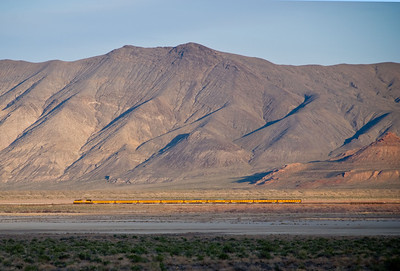 This train is dwarfed by the size of the surrounding mountains.  This photo was taken while driving from Reno to Winnemucca Nevada on the interstate highway.