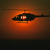 Silhouette of a Bell Long Ranger medical helicopter and a flight nurse in flight.