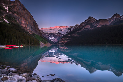 Beautiful Alpen glow on Victoria Glacier and stunning blue green water of Lake Louise.
