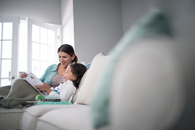 Mother helping daughter read on the couch.
