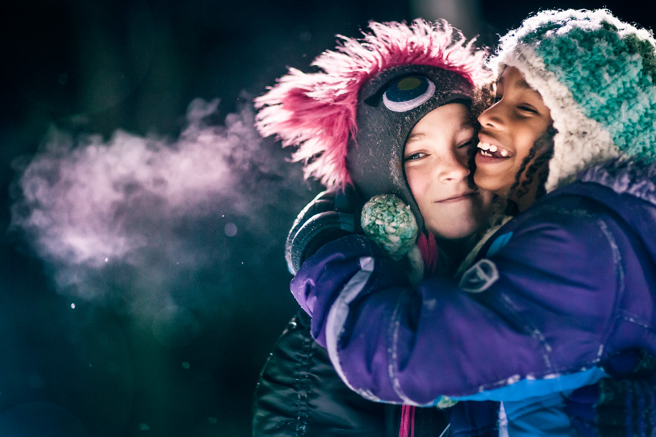 Two little girls hugging in the winter.