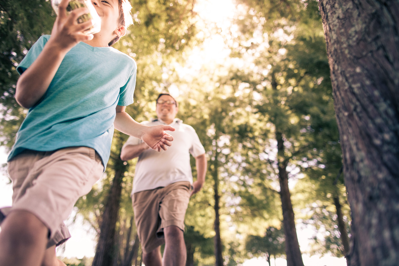 Dad chasing son in park.