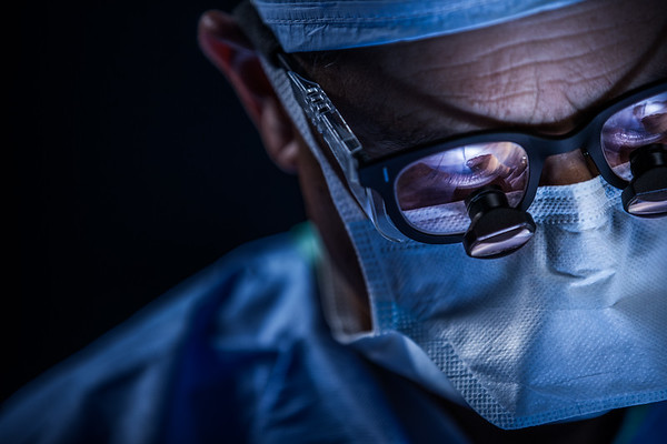 extreme closeup of doctor in surgery wearing loupe glasses