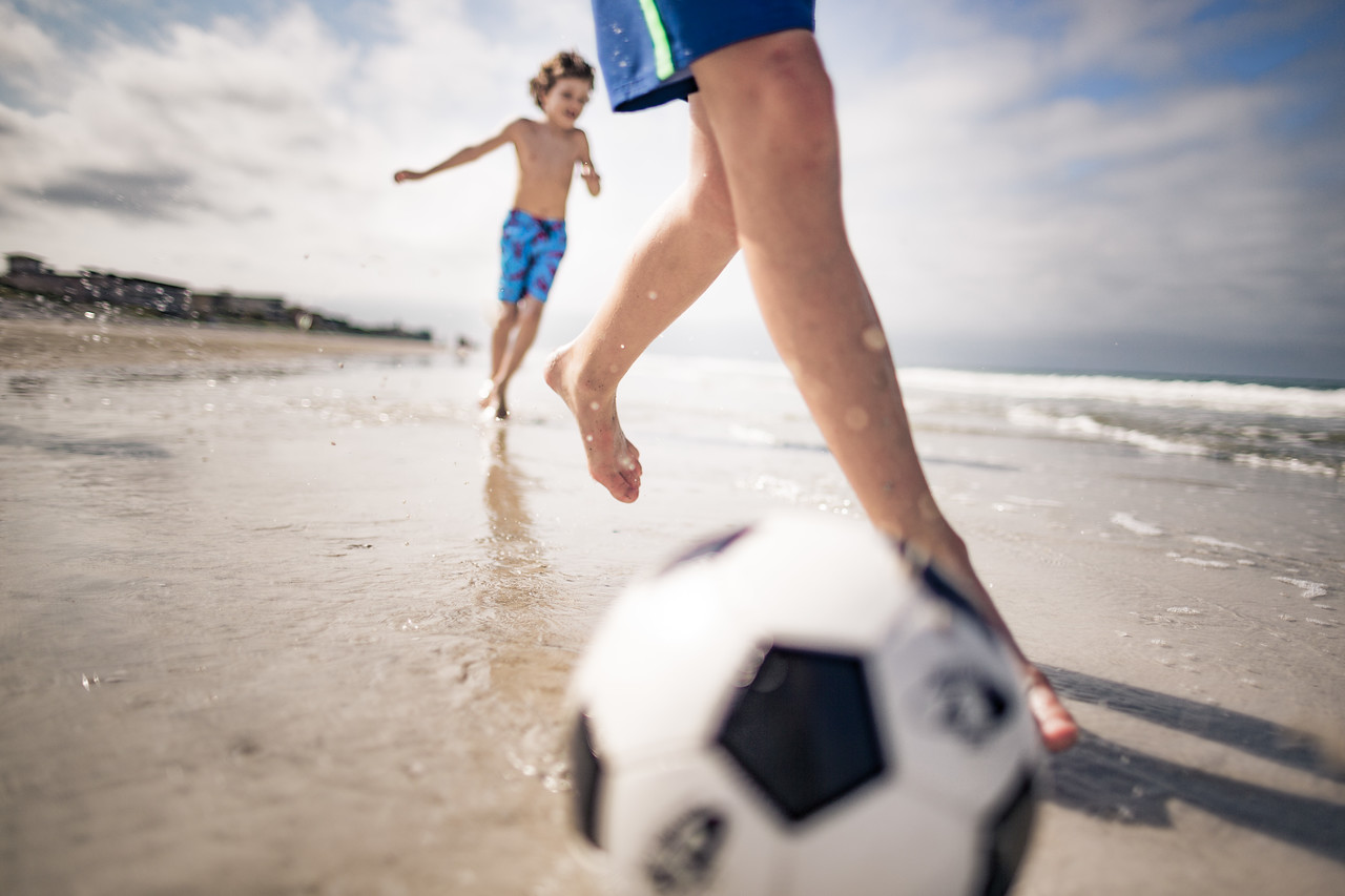Two young kids chasing a soccer ball on the beach.