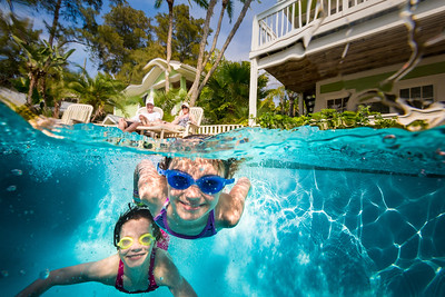 Brother and sister swimming underwater.
