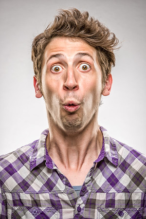 The funny face of a Caucasian man with short curly brown hair and a surprised expression.