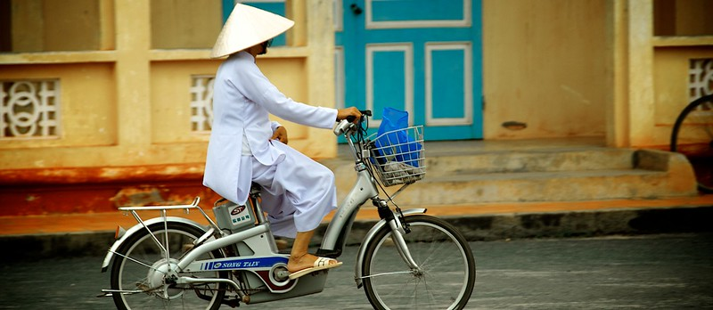 Nun riding outside Cao Dai Temple, Saigon, Vietnam