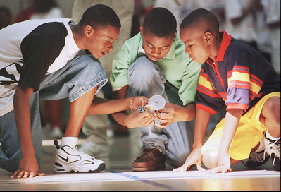 "Sentoris Bronner, left, 13, Nartaryus Coleman, center, 13, and Montarious Knight, 13, all 7th-graders at Broadstreet Junior High School in Shelby, Miss., make last minute adjustments to their contest entry during the ""Mousetrap Car Competition"" portion of the 1998 Southeastern Consortium for Minorities in Engineering (S.E.C.M.E.) Student Competition, Friday, April 3, 1998, on the campus of The University of Mississippi, in Oxford. Contestants constructed cars from ordinary mouse-traps and awards were given based on the distance the vehicles were able to travel, powered only by the mouse-trap's spring. (AP Photo/Joe Ellis)"