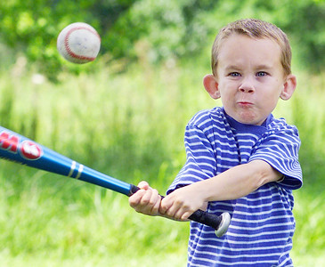 Garrett Nichols, 7, concentrates on a pitch from his Dad Scott Nichols as the pair play ball outside their house in Richland Monday afternoon. In June, Scott and Garrett will travel to Birmingham, Ala. where Garrett will receive one of his father's kidney's in a transplant operation.
