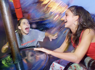 Not letting a little rain dampen their spirits, Mary Stephens (left) and Marianna Peragallo, both of Madison, enjoy a wild ride aboard the Tornado on Wednesday at opening night of the Mississippi State Fair in Jackson.