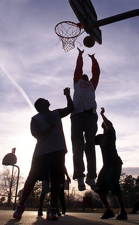 Marcus Allen (center) of Jackson lays the ball up and in as he and a group of friends take advantage of unseasonably mild weather Monday afternoon during a pick-up basketball game at Battlefield Park in Jackson.